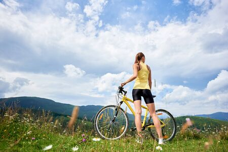 Back view of young woman cyclist standing on a grassy hill with yellow mountain bicycle, enjoying summer day in the mountains. Outdoor sport activity, lifestyle concept