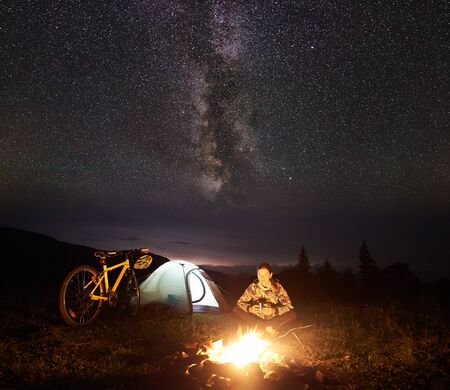 Young woman cyclist resting at night camping near burning campfire, illuminated tourist tent, mountain bike under incredible beautiful evening sky full of stars and Milky way. Tourism concept