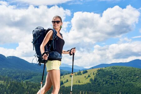 Beautiful smiling woman hiker hiking in Carpathian mountain trail, wearing backpack and sunglasses, using trekking sticks, enjoying summer sunny day in the mountains. Tourism concept