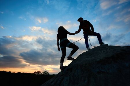 Silhouettes people in danger helping each other concept. Man friendly hand helping woman going upstairs the edge of mountain. Young couple outdoors on beautiful dawn and amazing clouds on background. Stock Photo