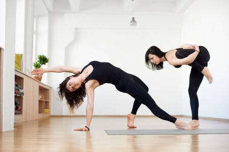 Two young women experienced athletes practicing different yoga poses and asanas. Partner yoga. Stretching standing balancing exercises and Wild thing pose, yogi in action in sport club studio