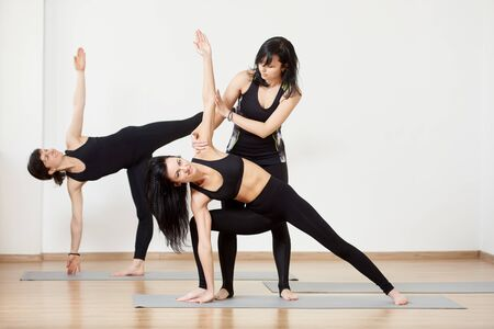 Female group in black sportswear exercising yoga. Lesson with trainer. Standing yoga poses practising. Instructor helping doing Extended side angle pose while another woman doing Half moon pose