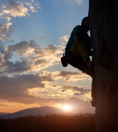 Male climber silhouette in action while climbing high up on challenging rocky route. Wonderful sunset and clouds on sky over mountains in twilight. Extreme, activity, recreation, rock climbing concept Reklamní fotografie
