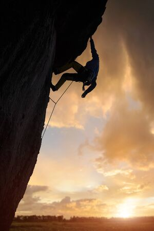 Low angle view of unrecognizable climber clinging to rock with one hand and looking down during extreme rock climbing. Cloudy sky and sunlight on horizon through cumulonimbus on background. Copy space