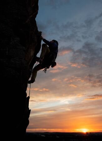 Male climbing in safety harness, looking up and taking decisive step on challenging rocky route. Side view. Wonderful sky during sunset on background. Copy space. Rock climbing and leadership concept Reklamní fotografie