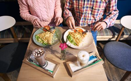 Cropped view of couple - man and woman sitting together in cafe at small table enjoying big pancake sandwich with vegetables. Coffee beverage and vase with flower on blurred foreground. Top view Banco de Imagens