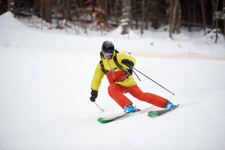Young skier performing skiing trick. Ski training during snowfall. Carving skiing technique. Winter activities, freestyle, adventure, thrill concept Banque d'images - 131577519