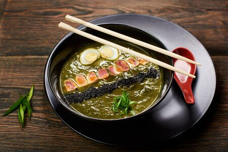 Bowl of delicious miso soup with egg, sesame, fish and chuka served on wooden table in asian restaurant