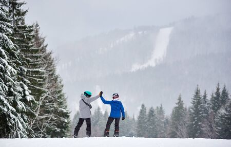 Back view of couple of snowboarders giving high five to each other, preparing descending from high slope with charming forest around during snowing in the mountains. Stok Fotoğraf