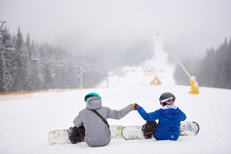 Back view of sportsmen couple sitting on snow before freeriding from ski run at ski resort. Man and woman doing fist bump. Snowfall in mountains. Friendship, support, decision, sport, extreme concept