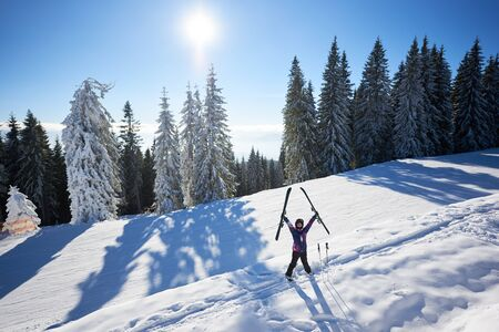 Happy smiling woman in helmet taking her ski in hands raised up and standing in middle of snow-covered mountain slope. Sunny day during winter vacation. Pine forest on background. Front general view.