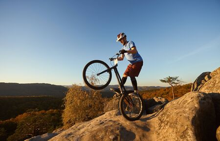 Fearless cyclist balancing on back wheel on trial bike. Sportsman rider making acrobatic stunt on the edge of big boulder on the top of mountain at sunset. Concept of extreme sport active lifestyle