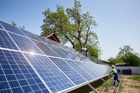 Two technicians installing solar panel photo voltaic system installation on steel platform on bright sunny summer day under blue sky. Renewable ecological green energy production concept.
