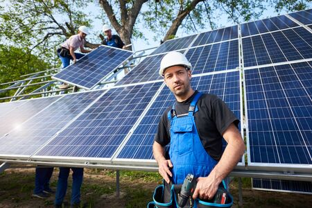 Portrait of smiling confident engineer technician with electrical screwdriver, standing in front of unfinished high exterior solar panel photo voltaic system with team of workers on high platform.