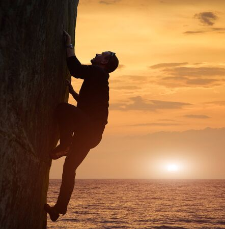 Side view of man in black climbing on rock without safety harness over sea in twilight. Recreational activities in nature. Copy space on orange sunset sky. Adrenaline, extreme, danger, bravery concept Banco de Imagens
