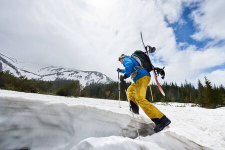Side view of male in winter mountain touring walking up with ski poles helping and carrying backpack and snowboard on his back. Ski touring and mountaineering promotion. Landscape view with copy space