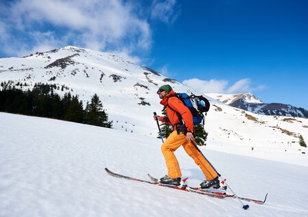 Skier tourist backpacker, happy bearded man hiking on skis up hill on background of blue sky and beautiful mountains ridges. Winter vacations, active lifestyle, skiing and trekking concept.