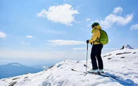 Back view of sportsman skier in helmet and goggles with backpack standing on skis holding ski poles in deep white snow, on copy space background of bright blue sky enjoying beautiful mountain view.