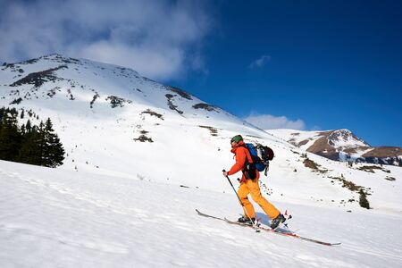 Skier tourist backpacker walking on skis up steep hill on background of bright blue sky and beautiful mountains ridges. Winter vacations, active lifestyle, skiing and trekking concept.