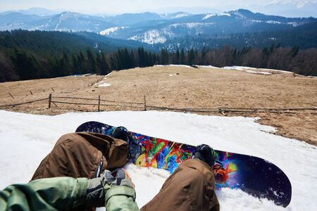 Point of view shot of snowboarder legs and bright colorful snowboard in snow, view of winter landscape. Mountain clearing among tall spruce trees, snowy peaks in background. Sports and pov concept.