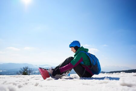 Snowboarder young woman in helmet with backpack sitting in snow adjusting snowboard on copy space background of blue sky and snowy mountain peaks. Extreme winter sports, active lifestyle concept.