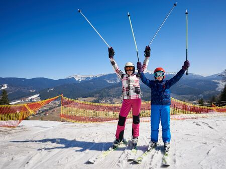 Two skiers, boy and girl in warm clothing and goggles on skis with raised poles in deep snow on background of winter ski resort, bright blue sky and beautiful mountains. Sports and recreation concept.