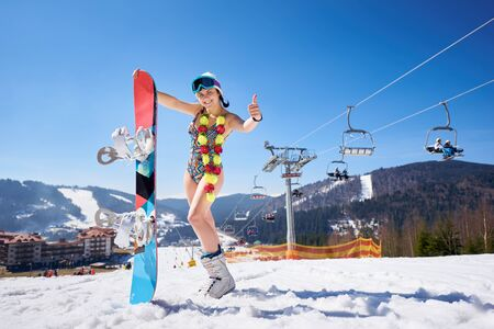 Attractive young female snowboarder in swimsuit with flower garland, ski boots and goggles holding snowboard on background of blue sky, winter mountain resort and ski lift. Sportive feast concept.