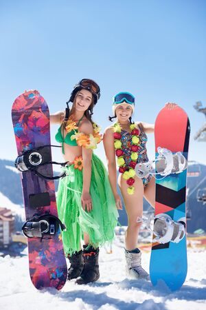 Two attractive smiling girls in exotic bright summer clothing and goggles with snowboards standing in snow on background of blue sky and winter mountains. Holidays, sports and celebration concept. 스톡 콘텐츠