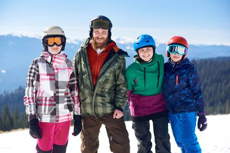 Group of happy people, man, woman and two kids smiling in camera on background of winter woody mountains, white snow and bright blue sky. Sport, recreation and friendship, family hobbies concept.