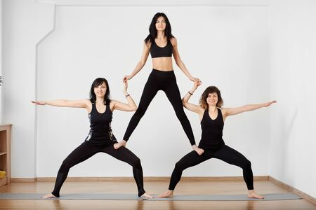 Young attractive smiling and concentrated group of acrobats standing in hip-opening yoga pose and creating pyramid. Practicing acro yoga balancing in white yoga studio space. Acro yoga concept