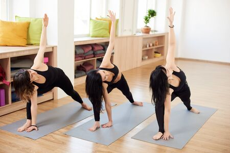 Female group of three experienced yogi practicing together in Extended side angle pose. Exercising with inclining, stretching and lifting hand up. Yoga classes in gym. Fitness and people concept 스톡 콘텐츠