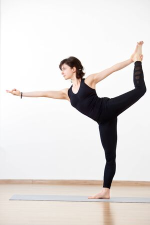Flexible woman, yogi performing stance in popular Lord of dance pose. Female athlete in black on white background. Concept of attraction to perfection, body and mind unity. Vertical side portrait