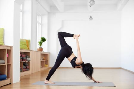 Advanced yoga. Young slender brunette woman in yoga class training stretching and exercises. Side view of girl doing One-legged downward-facing dog pose. Healthy lifestyle in moder fitness club 스톡 콘텐츠