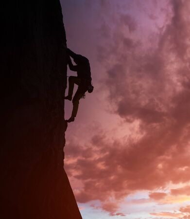 Male silhouette rock climbing and doing next step. Rock climber in action on cliff. Dark purple cloudy sky on background with copy space. Low angle view. Dangerous, extreme, endurance, victory concept