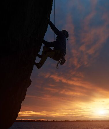 Silhouette of athletic person in safety harness hanging on edge of challenging cliff. Climber on rope rock climbing on cliff over water at sunset. Concept of mountaineering, adventure and challenge