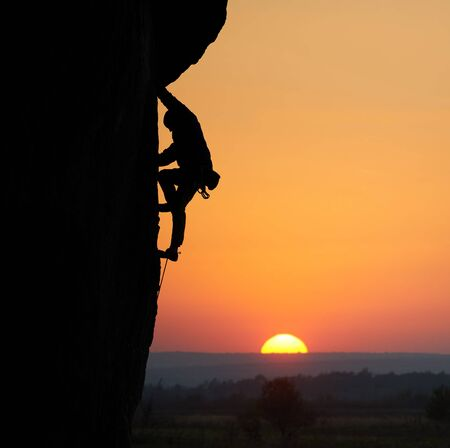 Silhouette of sportsman rock climbing up to top goal. Orange sky with sunset on horizon with wide valley on background. Persistence, success, strength, achievement, extreme concept. Copy space