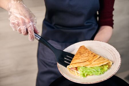 Chefs female hands keeping white plate and putting in with spatula sandwich crepe with green salad and rolled up in triangle. Dish serving process. Appetizing hot fried food for lunch. Close up view.