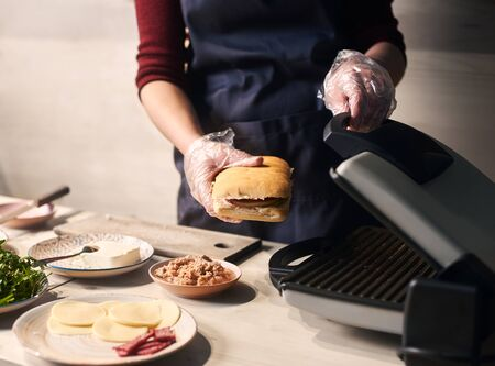 Using special grill equipment in cooking original american street popular food. Detailed of chef baking gourmet sandwich. Process of cooking typical italian refreshments. Gray background. Side view. 스톡 콘텐츠