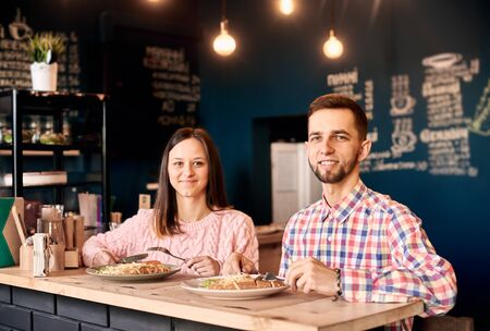 Stylish brunette smiling young couple sitting one by one at bar table and looking at camera. Enjoying appetizing lunch food and beverages in atmospheric restaurant. Blue decorated wall on background. 스톡 콘텐츠