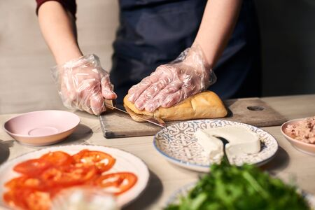 Focus on hand cutting with knife long bread roll on cutting board for preparing grilled panini sandwich. Ingredients on blurred foreground: tomato slices, tuna, butter, salad on plate at wooden table.