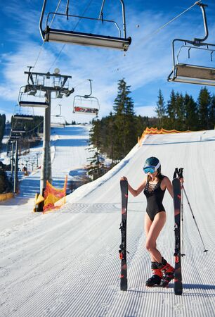 Sexy attractive young woman in black swimsuit, helmet and goggles holding skis and poles on background of mountains resort ski lift on sunny winter day. Extreme sports and recreation concept.