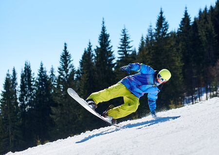 Snowboarder man in goggles and helmet riding snowboard fast down steep snowy mountain slope on background of blue sky and spruce trees on sunny winter day. Extreme sport and recreation concept.