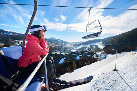 Happy female tourist is sitting on chairlift in mountain resorts. Girl in a ski suit at an altitude and shows with hand on snow-capped mountains