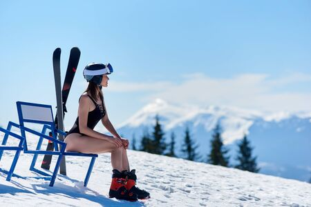 Skier girl in black swimsuit and helmet, sitting at a bench near skis and enjoing wonderfull view at the mountains on ski resort. Blue sky, forests, mountains on the background. Ski season concept 스톡 콘텐츠