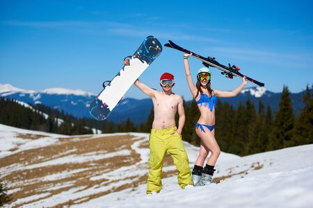 Happy young couple in goggles, sexy woman in bikini and snowboarder man with bare torso holding skis and snowboard in raised arms standing on snowy hill on background of blue sky and winter mountains.