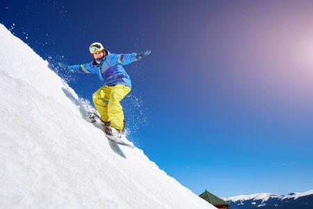 Guy snowboarding down the mountain slope. Portrait of young man snowboarding in winter against blue sky. Clear weather and sky, prepared snow