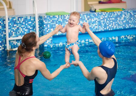 Two women holding happy laughing baby doing exercising over water in air during swimming classes. Useful, active and joyful leisure pastime for little child baby with mother. Relaxing in swimming pool 스톡 콘텐츠