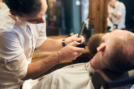 Young hardworking barber standing near his client sitting in hairdresser chair. Close up view of beard shaving process. Business, service, masculine style, hair care, barbershop concept. Back view. Reklamní fotografie
