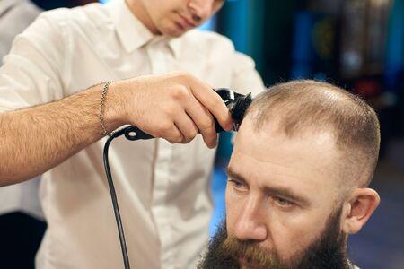 Electric trimmer machine in skillful barbers hand, cutting short hair on clients head. Concept of modern hairdressing tools and methods. Adult bearded man in barbershop. Cropped close up view.