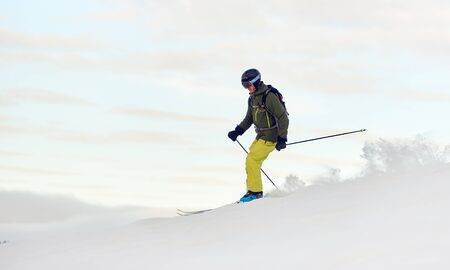 Young sportsman in helmet and goggles enjoying process of skiing on winter vacation. Male skier on slope in mountains. Recreational outdoors concept. Side view. White monochrome. Copy space for banner